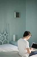 Young man sitting on side of bed, typing on laptop