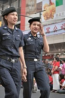 Thai police women hold hands while walking on street in Chinatown, Bangkok, Thailand No model releases available