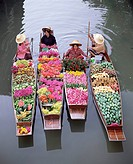 A group of four women market traders in boats laden with fruit and flowers, Damnoen Saduak floating market, Bangkok, Thailand, Southeast Asia, Asia