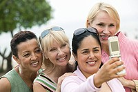 Group of middle_aged women photographing themselves with a mobile phone