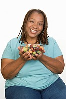 Portrait of Mid_adult overweight woman holding bowl wit fruit salad and smiling