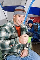 Man drinking in front of tent