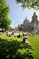 Belfast City hall with crowd sitting relaxing in the May sunshine