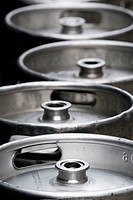 A line of empty aluminum beer kegs sitting on the street wait collection