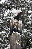 Raven totemic figure on Tlingit totem pole at Auke Bay recreation area. Winter in Southeast Alaska.