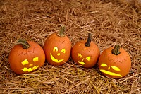 Close up of small Jack_O_Lanterns sitting in hay.