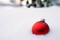 Red Christmas ball placed in snow blurred foreground and background winter Alaska