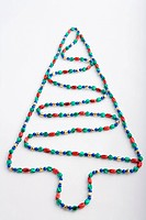 Closeup of Christmas tree made with colorful bead strands on white background studio portrait