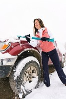 Woman brushing heavy snow off vehicle using snowbrush Cedar City Utah Winter