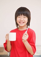 Elementary school boy holding toothbrush and cup