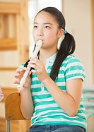 Elementary school girl playing recorder