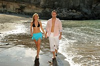 Married couple walking on beach