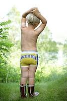 Ljushårig Liten Pojke Står I Gräset Med Bar Överkropp, Iklädd Gummistövlar Och Kalsonger Som Det Står Sverige På. Boy5_6 Years Shirtless Standing On G...