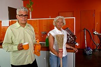 Senior couple with cleaning utensils in the kitchen