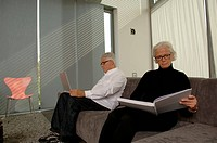 Senior man with a laptop next to a senior woman with a book, both sitting on a settee
