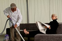 Senior man vacuuming, senior woman sitting on sofa while reading a newspaper
