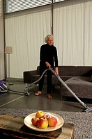 Senior woman vacuum_cleaning the floor of a modern appartment