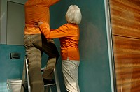 Senior woman holding man standing on a ladder