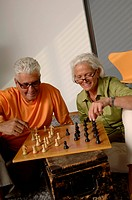 Senior man and woman playing chess together, close_up