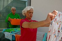Senior man helping a senior woman hanging laundry on a line