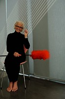 Senior woman holding a feather duster sitting on chair