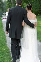 Bridegroom taking his Bride over a Gravel_Path _ Meadow _ Wedding