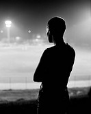 Kvinna tittar på upplyst stadium om kvällen. Silhouette Of Woman Looking At Illuminated Sport Stadium At Night B&W
