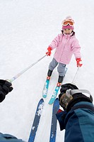 Girl skiing with father, smiling