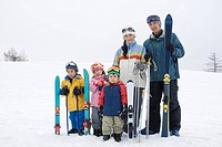 Portrait of family holding skis on snow, smiling and looking at camera