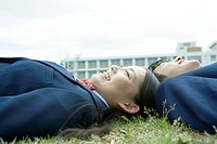 High school students lying on lawn, smiling, close up