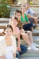 Portrait of young people sitting on wooden stairs, smiling