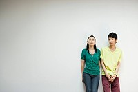 Young Japanese Couple Standing against Wall