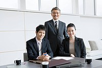 Business Scene, Two Men and Woman in Conference Room, Looking at Camera