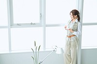 The Japanese Woman Who Stands With A Cup By The Window
