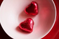 Two heart shaped candies in bowl (close-up, directly above)