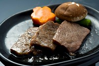 Slices of grilled beef and vegetables on a plate, high angle view, close up, black background, Japan