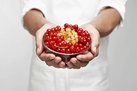 Chef holding bowl of red and white currants mid section