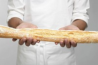 Chef holding baguette mid section (thumbnail)