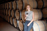 Woman drinking red wine by wine barrels portrait