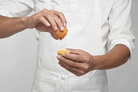Chef cracking brown egg mid section