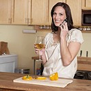 Mid_Adult Woman on Phone While Cooking