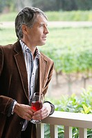 Mid adult man drinking red wine on patio portrait (thumbnail)