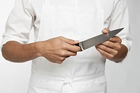 Chef holding kitchen knife (mid section)