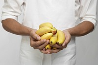 Chef holding bunches of bananas mid section