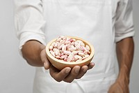 Chef holding bowl of borlotto beans mid section