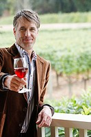 Mid adult man toasting with red wine (portrait)