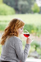 Young woman smelling red wine