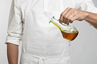 Chef pouring olive oil mid section