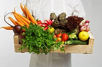 Chef holding box of vegetables mid section