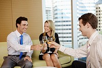 Three businesspeople toasting with white wine